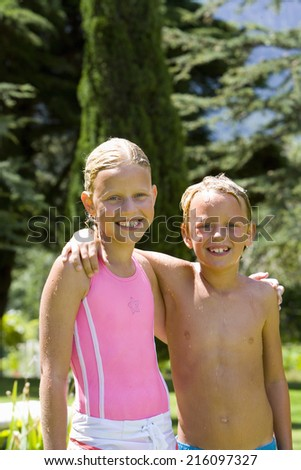 Brother and sister (6-10) arm in arm, in swimsuits, smiling, portrait - stock photo