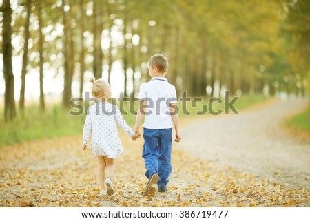 Brother and sister Autumn road - stock photo