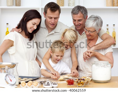 Brother and sister baking in the kitchen with their grandparents and parents - stock photo