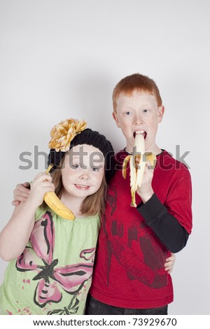 Brother and Sister being silly with Bananas. - stock photo