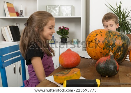 Brother and sister  carving jack o lanterns on Halloween - stock photo