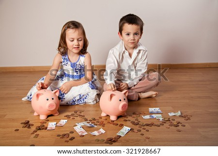 Brother and sister collecting money in the piggy bank - stock photo