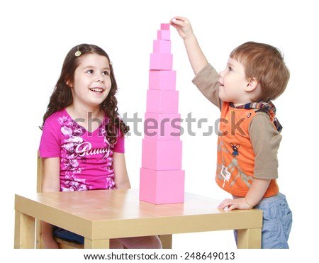 Brother and sister collects Red Pyramid in the Montessori kindergarten.Isolated on white background, Lotus Children's Center - stock photo