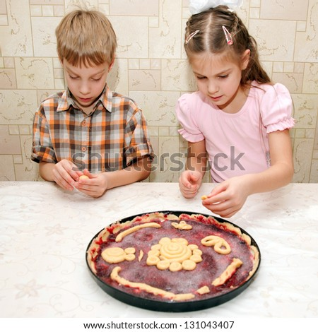 Brother and sister cooking a pie together - stock photo