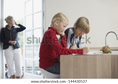 Brother and sister doing homework in kitchen with mother in background - stock photo