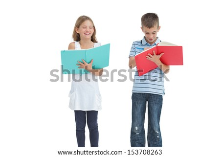 Brother and sister doing their homework together while posing on white background - stock photo