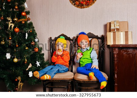 Brother and sister eating apples sitting on a chair next to the Christmas tree. Cute little kids. Happy family and Merry Christmas. - stock photo