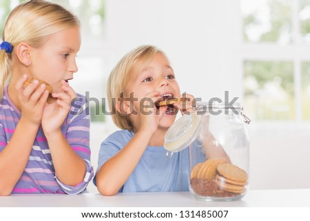 Brother and sister eating biscuits in the kitchen - stock photo