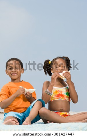 Brother and sister eating sandwiches - stock photo