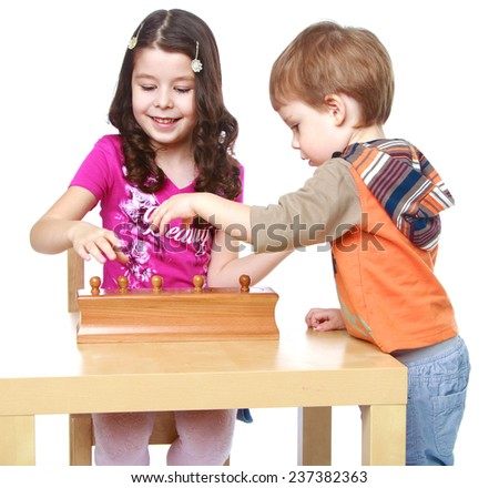 brother and sister enthusiastically collected puzzle.Isolated on white background portrait. - stock photo