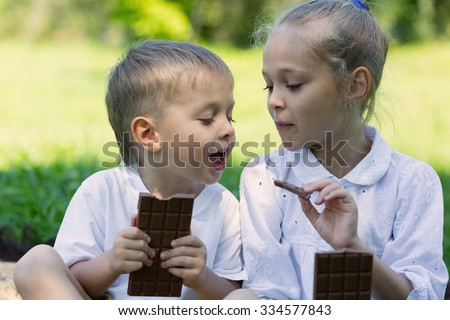 Brother and sister having fun eating chocolate outdoors. Summer day in park. - stock photo