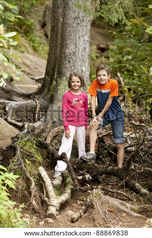 brother and sister hiking in deep forest - stock photo