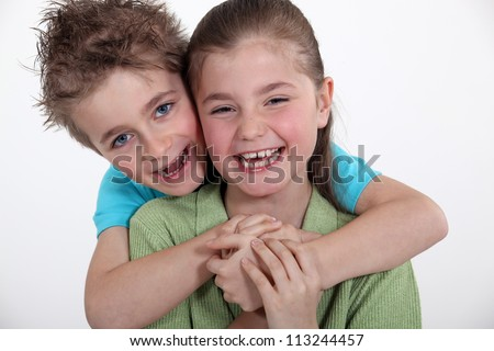 Brother and sister hugging. - stock photo