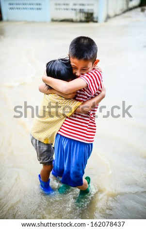 Brother and sister in blue boots holding togetherin flood disaster. - stock photo