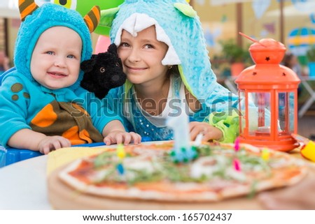 Brother and sister in costumes of monsters with dog toy in a cafe with pizza - stock photo