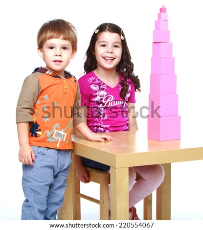 brother and sister in the Montessori school collects pyramid sitting at the table.The concept of development of the child, the child's upbringing. - stock photo