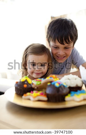 Brother and sister looking at colorful confectionery - stock photo