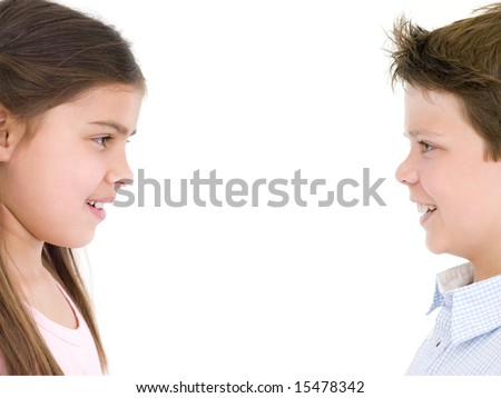 Brother and sister looking at each other smiling - stock photo