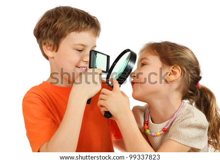 Brother and sister looking at each other through magnifying glasses isolated on white background; focus on lenses - stock photo