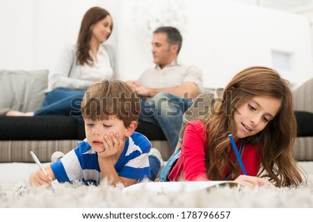 Brother And Sister Lying On Carpet Drawing, In Front Of Parents - stock photo
