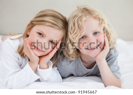 Brother and sister lying on the bed together - stock photo