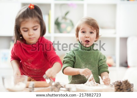 Brother and sister making cookies in a kitchen  - stock photo
