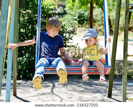 brother and sister on the swing in the park - stock photo