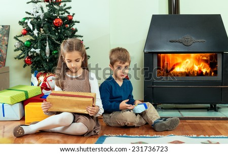 Brother and sister opening Christmas gifts in front of Christmas tree. - stock photo