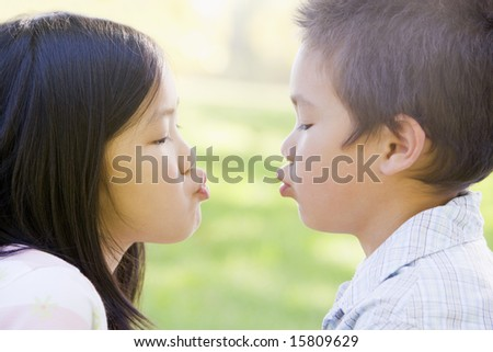 Brother and sister outdoors with eyes closed puckering up - stock photo