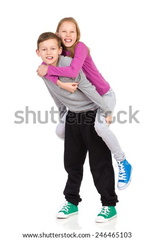 Brother and sister piggyback. Smiling boy carrying his sister on his back. Full length studio shot isolated on white. - stock photo