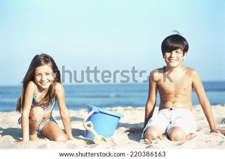 Brother and sister play in the sand at the beach - stock photo