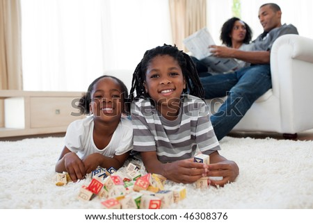 Brother and sister playing alphabetic cubes lying on the floor - stock photo