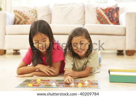 Brother and Sister Playing Board Game At Home - stock photo