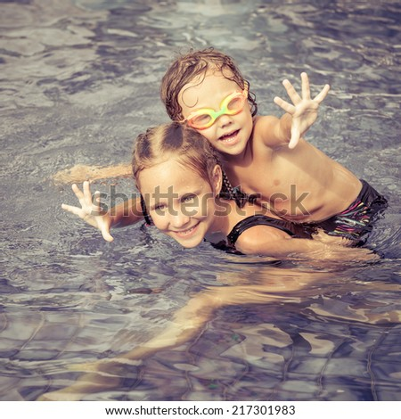 brother and sister playing in the swimming pool at the day time - stock photo
