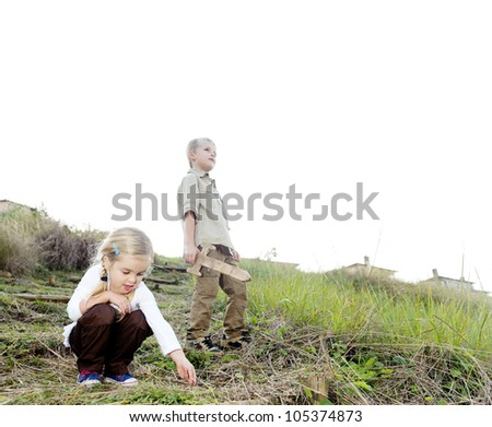 Brother and sister playing outdoors, exploring with wooden sword and being kids together - stock photo