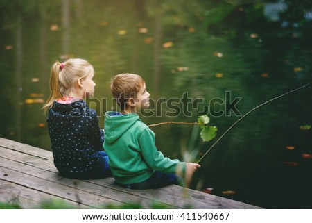 Brother and sister playing outside - imitate fishing at a lake - stock photo