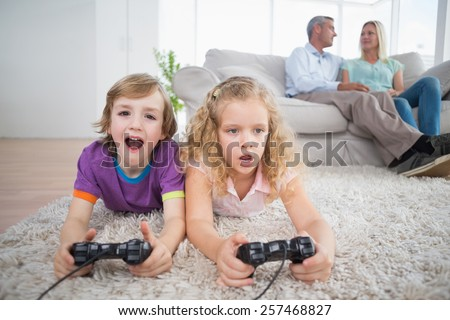 Brother and sister playing video game while parents sitting on sofa at home - stock photo