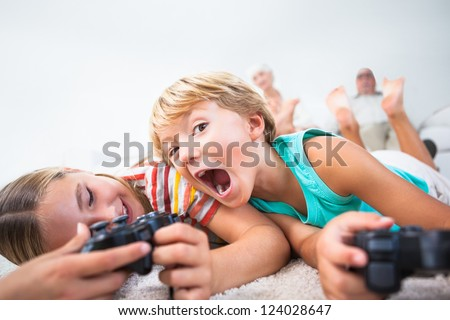Brother and sister playing video games and having fun on the floor - stock photo