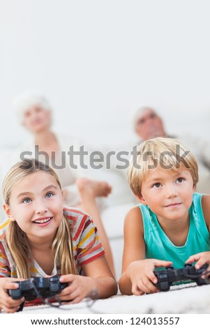 Brother and sister playing video games together on the floor - stock photo