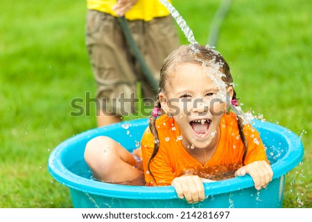 brother and sister playing with water near a house at the day time - stock photo