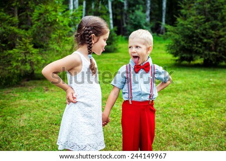 brother and sister shows their tongues - stock photo