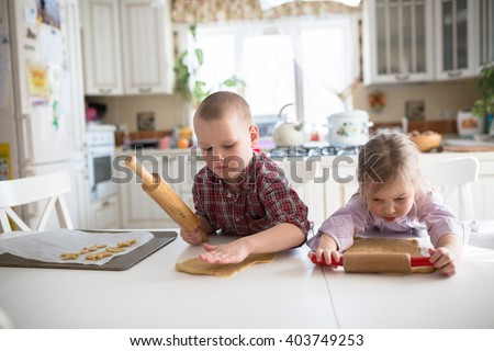 brother and sister siblings bake cookies, the dough is rolled out, casual lifestyle photo series in real life interior - stock photo