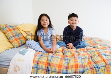 Brother and sister sitting on bed together - stock photo