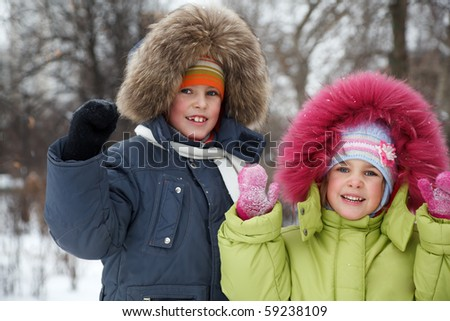 Brother and sister smiling looking into camera in winter forest. - stock photo