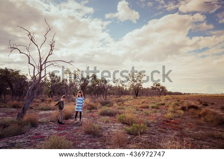 Brother and sister standing beside an old tree in outback Australia - stock photo