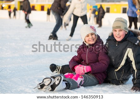 Brother and sister together fell while skating in rink - stock photo