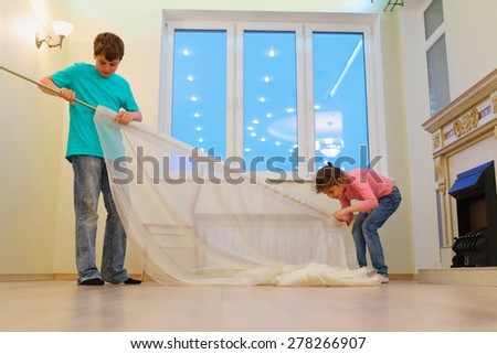 Brother and sister together hanging curtains in new apartment in evening - stock photo