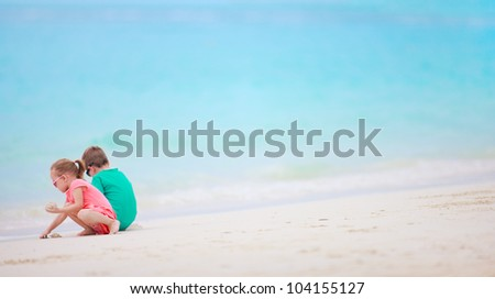 Brother and sister together on tropical beach - stock photo