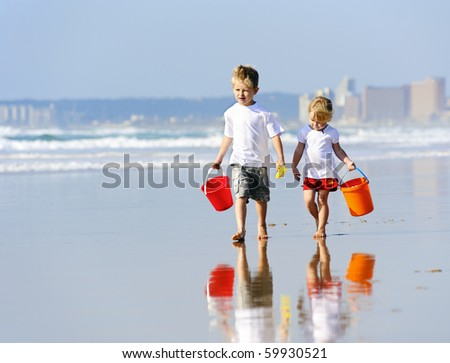 Brother and sister walk along the ocean edge looking for shells - stock photo