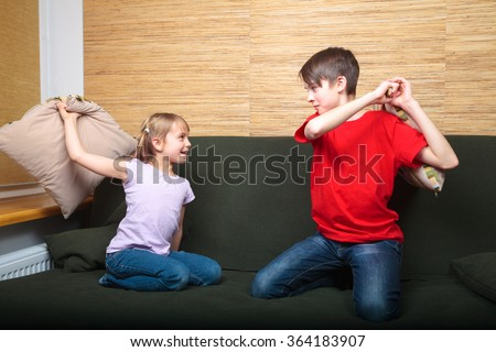 Brother and sister  wearing casual clothes  playing on a green sofa at home fighting with pillows - stock photo